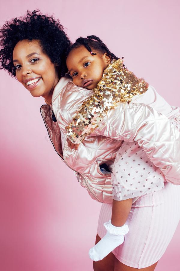 Young pretty african-american mother with little cute daughter hugging, happy smiling on pink background, lifestyle royalty free stock photos