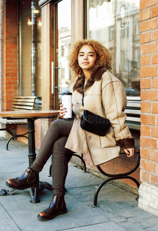 Young pretty african american women drinking coffee outside in cafe, modern business woman lifestyle concept. Young pretty african american woman drinking coffee stock photos