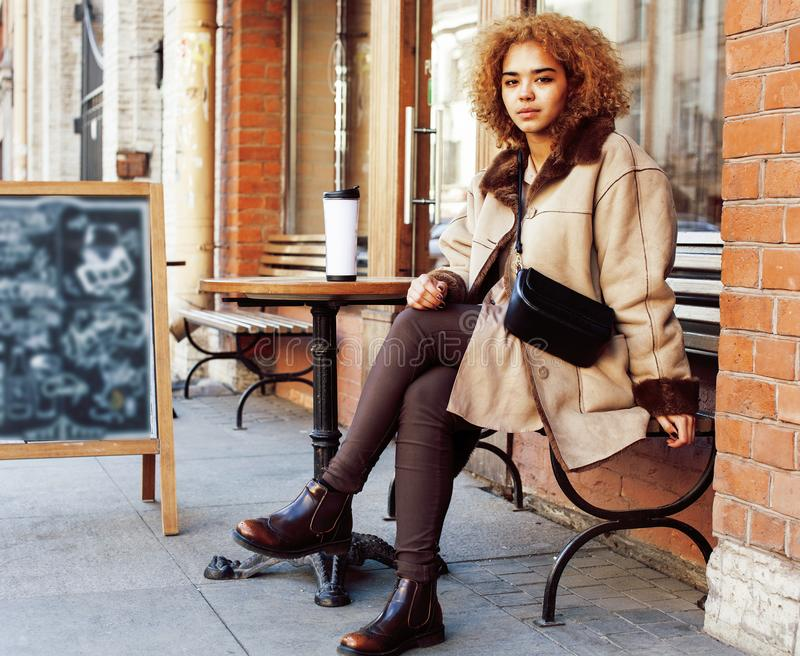 Young pretty african american women drinking coffee outside in cafe, modern business woman lifestyle concept. Young pretty african american woman drinking coffee royalty free stock photography