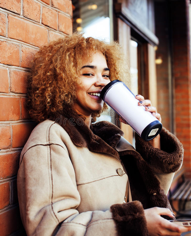 Young pretty african american women drinking coffee outside in cafe, modern real business woman lifestyle concept. Young pretty african american woman drinking royalty free stock image