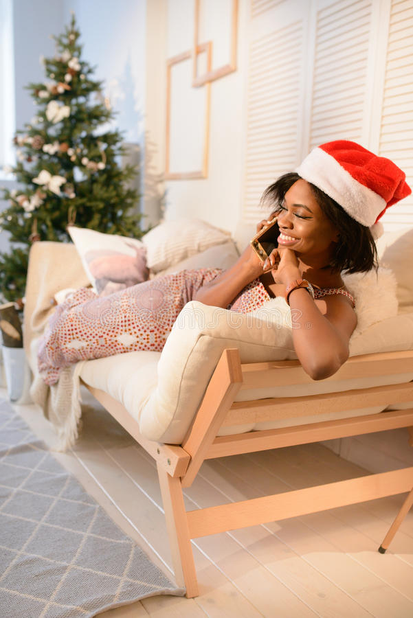 Young pretty african girl lying on the sofa and talking on the phone near the Christmas Tree stock image
