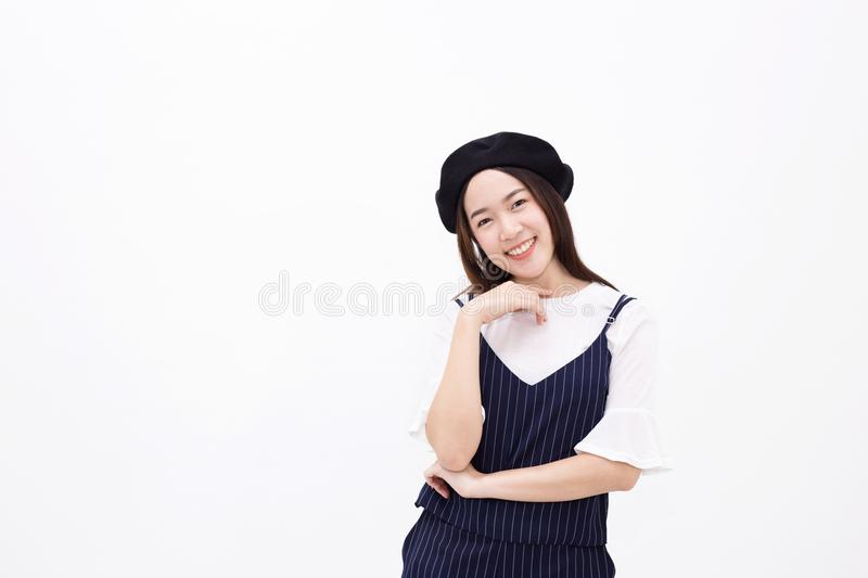 Young and pretty Asian female with artist hat smiling and posing in white isolated background royalty free stock images