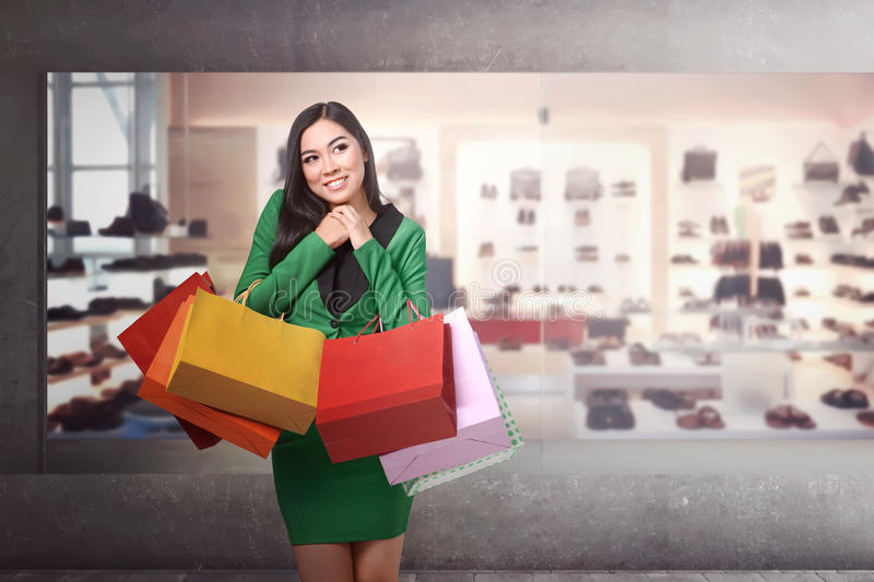 Young pretty asian girl standing in front of a store royalty free stock photography