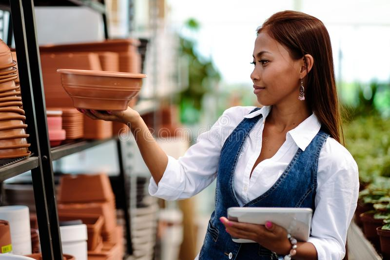 Young pretty Asian woman agronomist with tablet working in greenhouse checking the storage inventory.  royalty free stock image