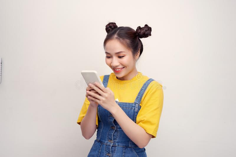 Young pretty Asian woman wearing a jeans dungaree and holding smartphone stock photo