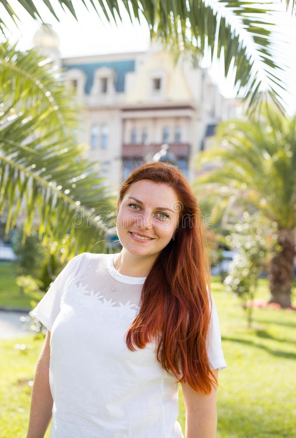 Young pretty attractive female looking around, walking on street of tropical city with palm trees and parked cars, sunny royalty free stock images