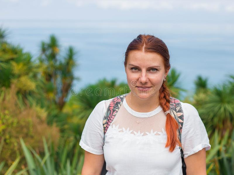 Young pretty attractive female with red hair looking around, walking on street of tropical city with palm trees , sunny royalty free stock image