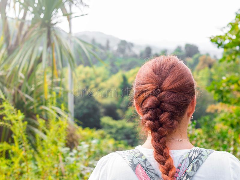 Young pretty attractive female with red hair looking on palm trees , sunny bright summer day royalty free stock images
