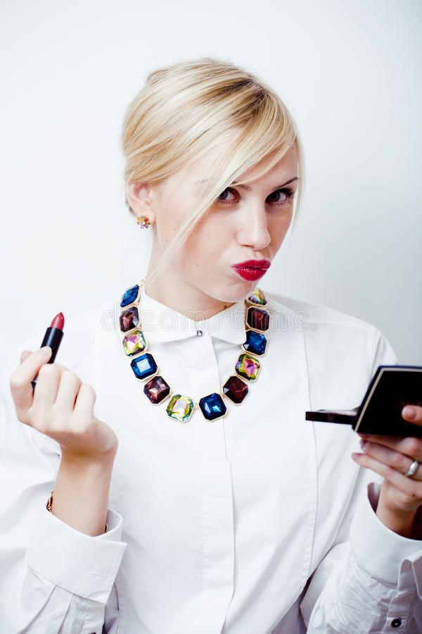 Young pretty blond girl with little mirror and red lipstick, lifestyle people concept stock images