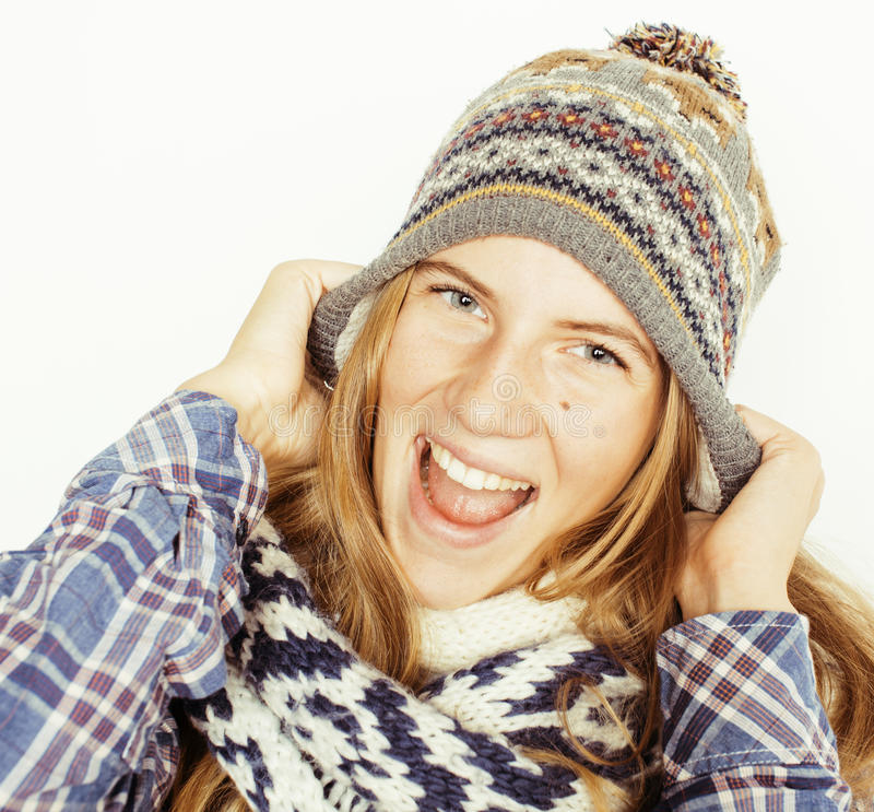 Young pretty blond teenage girl in winter hat and scarf on white background smiling close up isolated stock images