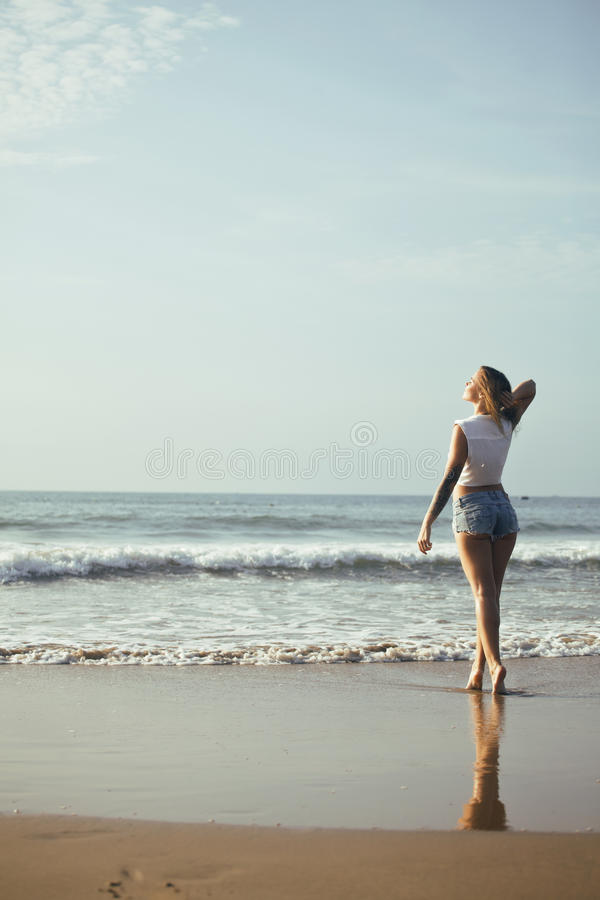 Young pretty blond woman at seacoast walking relaxing, fashion lady at sunset stock images