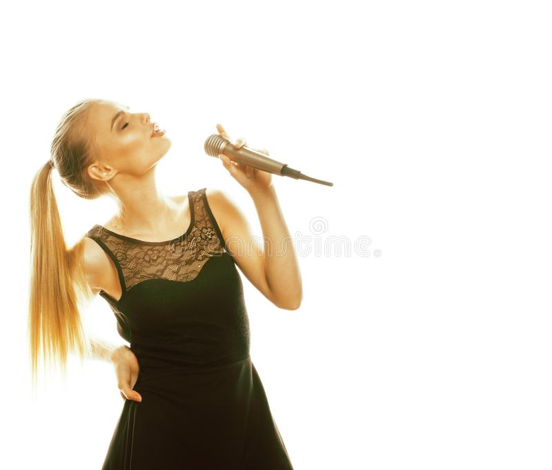 Young pretty blond woman singing in microphone isolated close up karaoke royalty free stock image