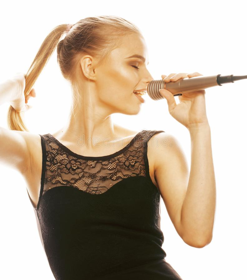 Young pretty blond woman singing in microphone isolated close up karaoke royalty free stock photo
