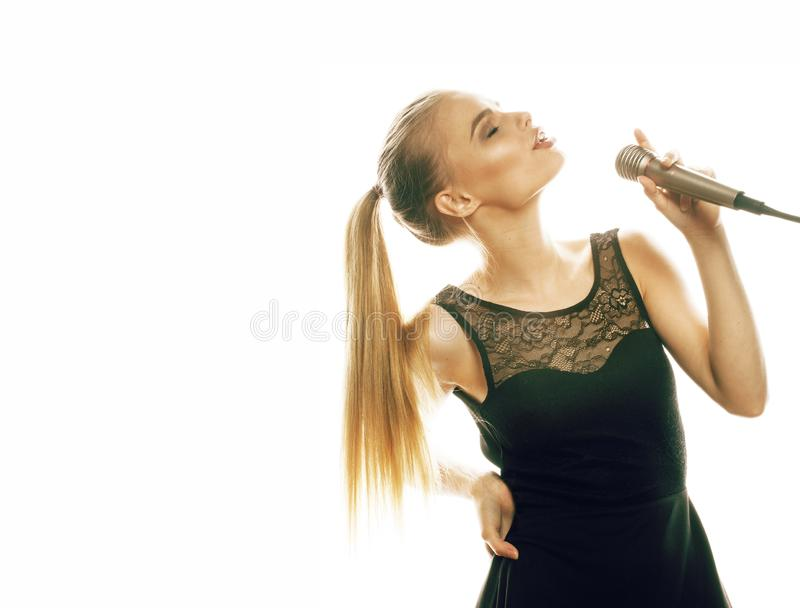 Young pretty blond woman singing in microphone isolated close up karaoke royalty free stock photos