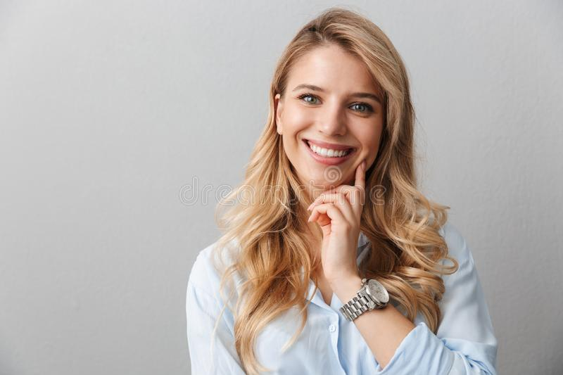 Young pretty blonde business woman posing isolated over grey wall background stock image