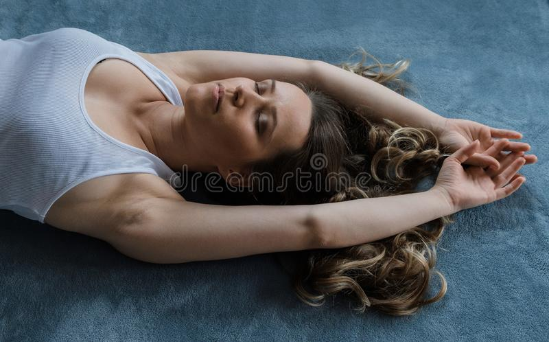 Young pretty blonde curly hair woman sleeps on a blue bed royalty free stock image