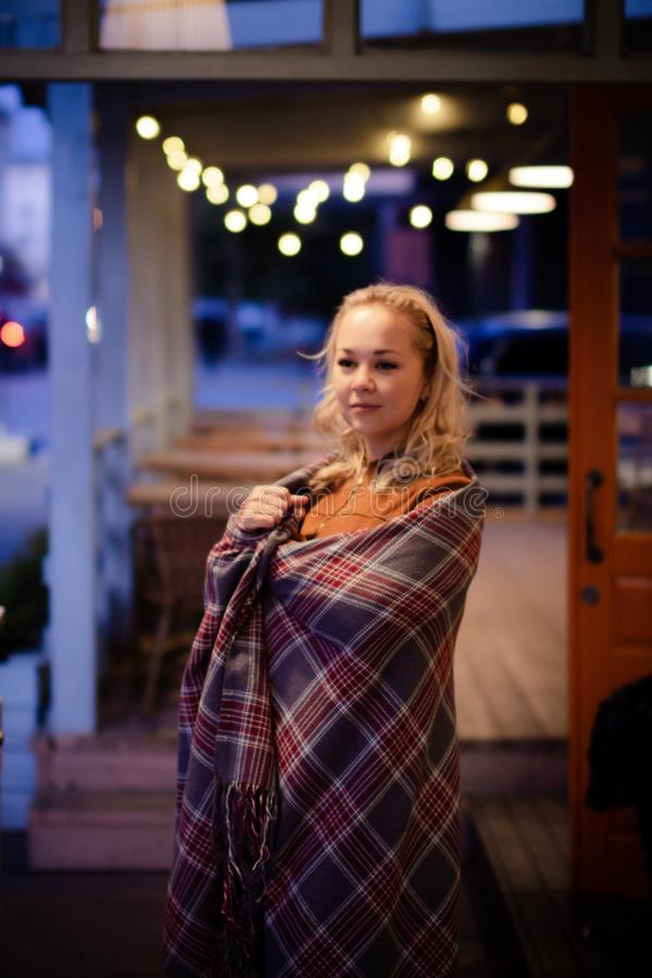 Young pretty blonde with a plaid on her shoulders on a cozy terrace on Christmas evening. Cozy autumn evening. stock photography