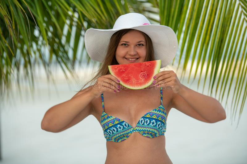 Girl with watermelon under palm tree. Young pretty blonde woman on the beach under palm trees wears hat and eats watermelon royalty free stock images