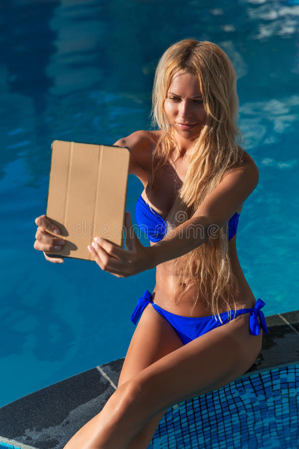 Young pretty blonde woman taking selfie photos swimming pool royalty free stock photo