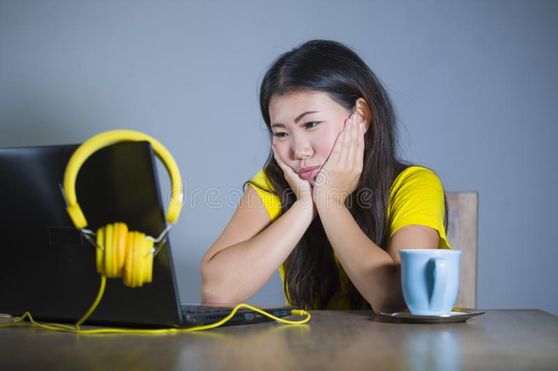 Young pretty and bored Asian Korean student girl working with laptop computer looking unhappy and sleepy holding face with hands royalty free stock photos