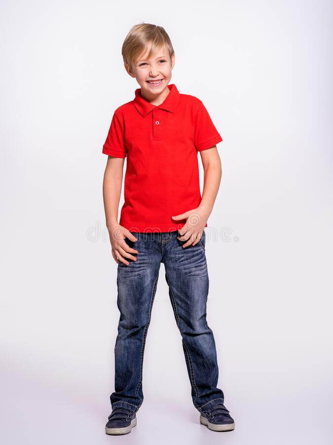 Young pretty boy posing at studio as a fashion model. Photo of a 8 years old kid. Full portrait of happy boy, isolated.  Portrait. Of white smiling kid in a red royalty free stock photos