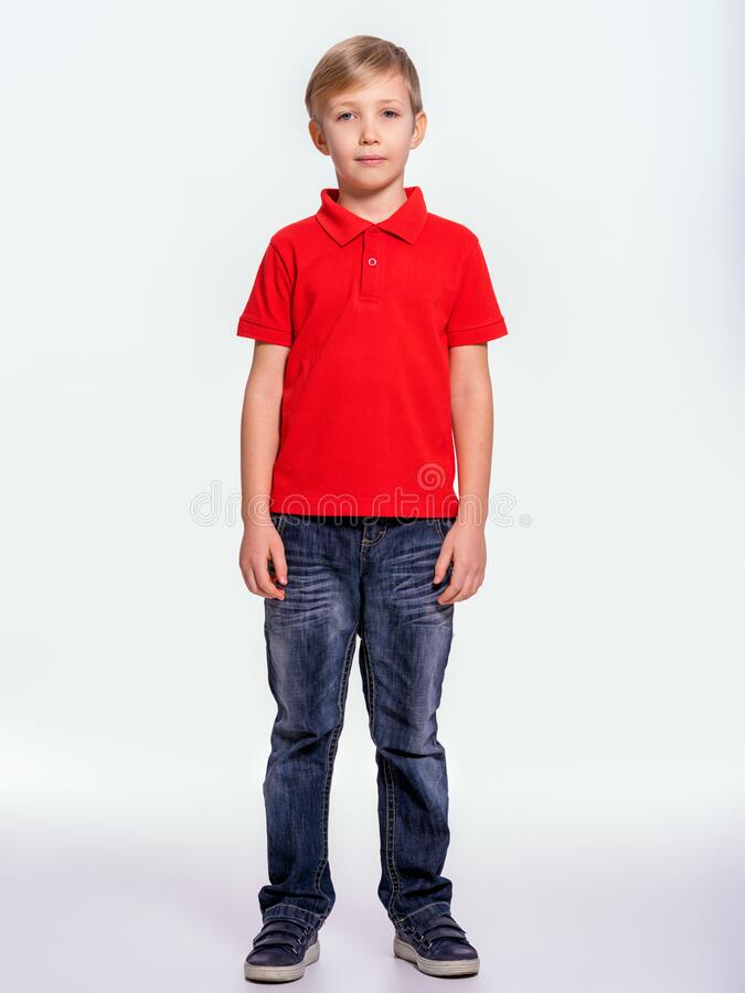 Young pretty boy posing at studio as a fashion model. Photo of a 8 years old kid. Full portrait of boy, isolated.  Portrait of. White kid in a red t-shirt and stock photos