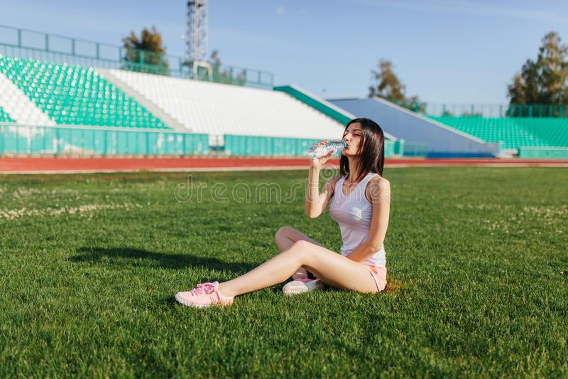 Young pretty brunette Caucasian girl in pink shorts and tank top in suit resting after sport run in the park on football stadium stock image
