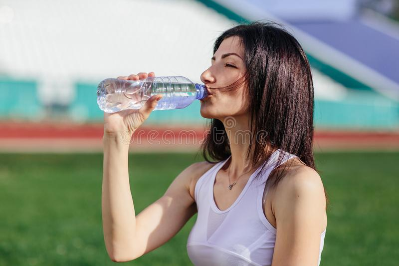 Young pretty brunette Caucasian girl in pink shorts and tank top in suit resting after sport run in the park on football stadium. On grass drinking water and royalty free stock images