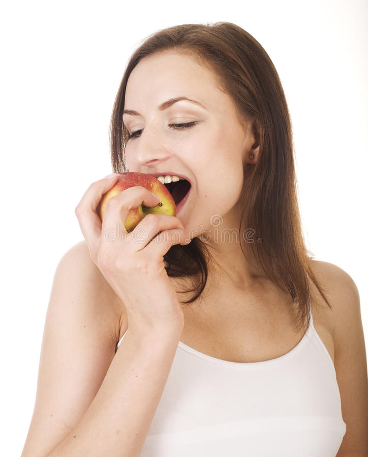 Young pretty brunette girl eating red apple stock photography