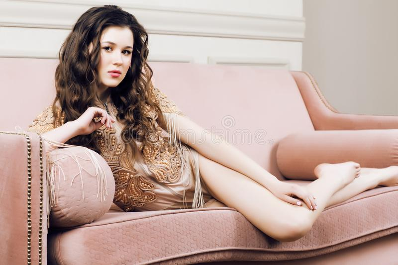 Young pretty brunette girl in fashion dress on sofa posing in lu. Xury rich home interior, lifestyle modern people concept close up stock image