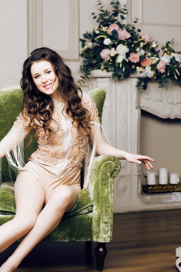 Young pretty brunette girl in fashion dress on sofa posing in luxury rich home interior, lifestyle modern people concept. Close up royalty free stock photos