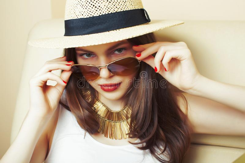 Young pretty brunette girl wearing hat and sunglasses waiting alone at home, lifestyle people concept stock photo