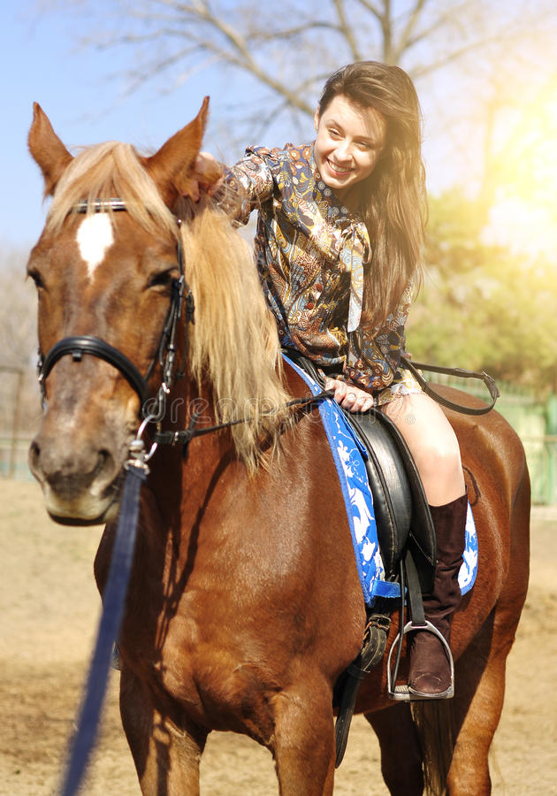 Young pretty brunette riding and caressing her horse outdoor royalty free stock images