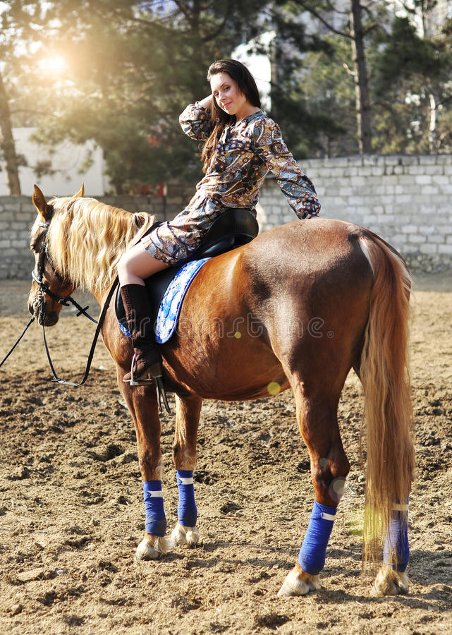 Young pretty brunette riding horse outdoor stock image