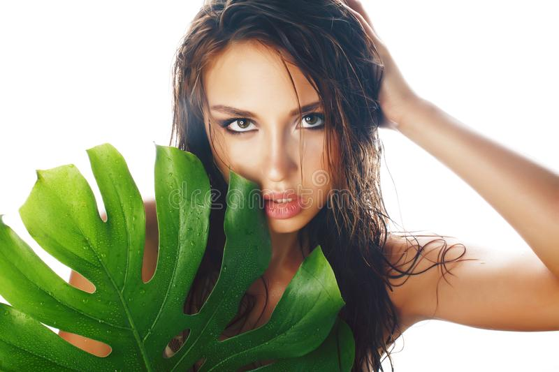 Young pretty brunette woman with big green leaf on white background isolated, spa care people concept royalty free stock images
