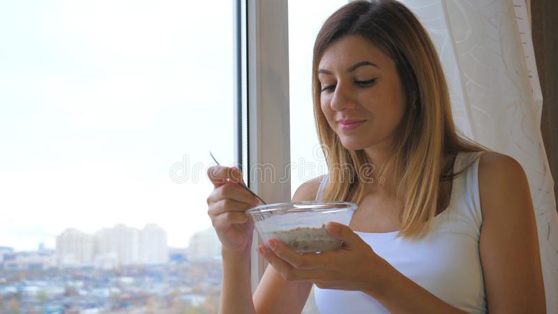 Woman Eating Cereal With Milk Out Of Bowl Standing At Window And Looking Outside stock photo