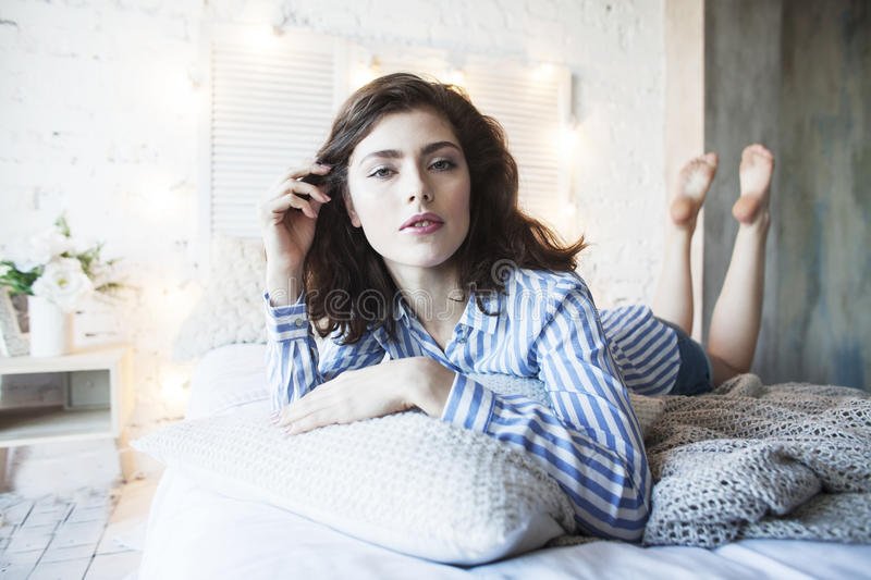 Young pretty brunette woman in her bedroom sitting at window, happy smiling lifestyle people concept. Close up stock image
