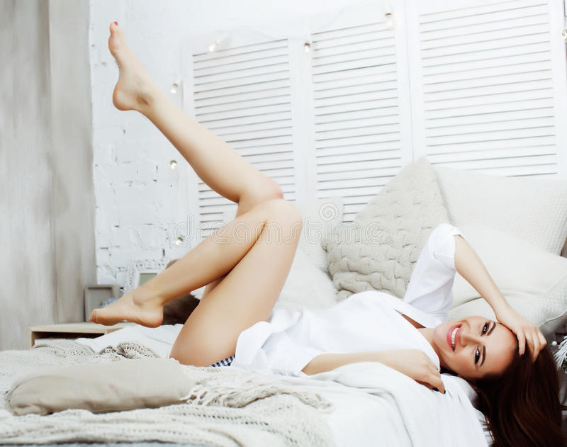 Young pretty brunette woman in her bedroom sitting at window, happy smiling lifestyle people concept royalty free stock image