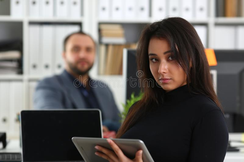 Young pretty brunette woman in office hold tablet in hands royalty free stock images