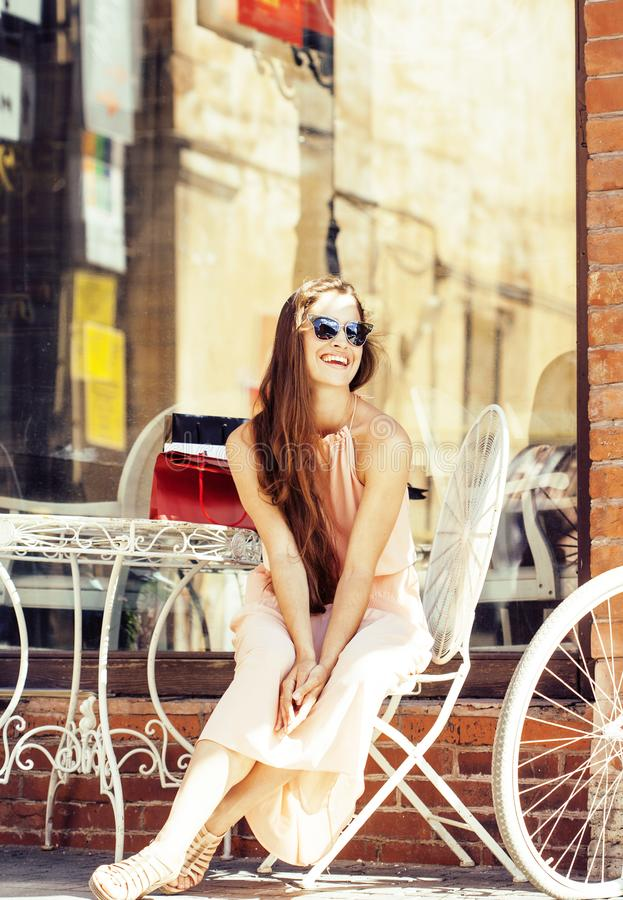 Young pretty brunette woman after shopping sitting at cafe outside on street smiling royalty free stock images