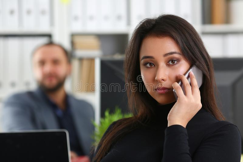 Young pretty brunette woman in office work with her boss hold smartphone in hands stock photos