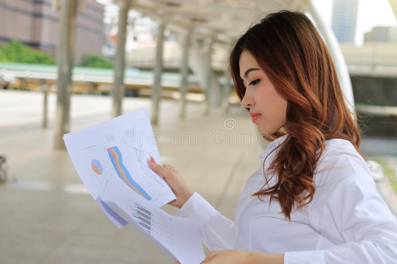 Young pretty business woman analyzing charts and graphs in her hands at public outdoor stock photos