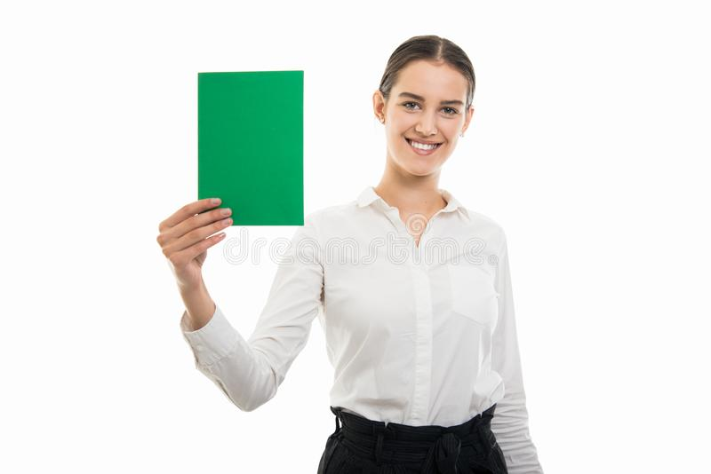 Young pretty business woman holding green cardboard and smiling royalty free stock photo