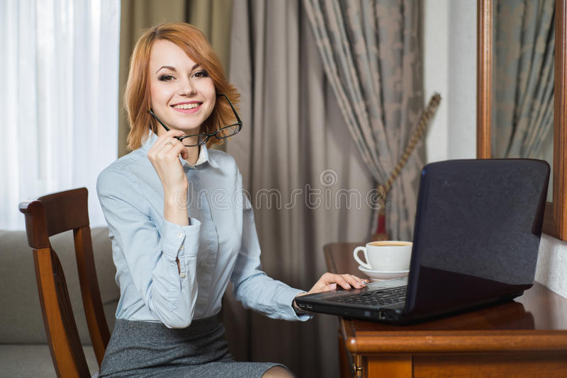 Young pretty business woman with laptop in the hotel room royalty free stock photo