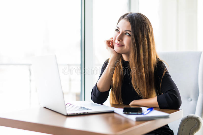 Young pretty business woman with notebook in the bright modern office stock image