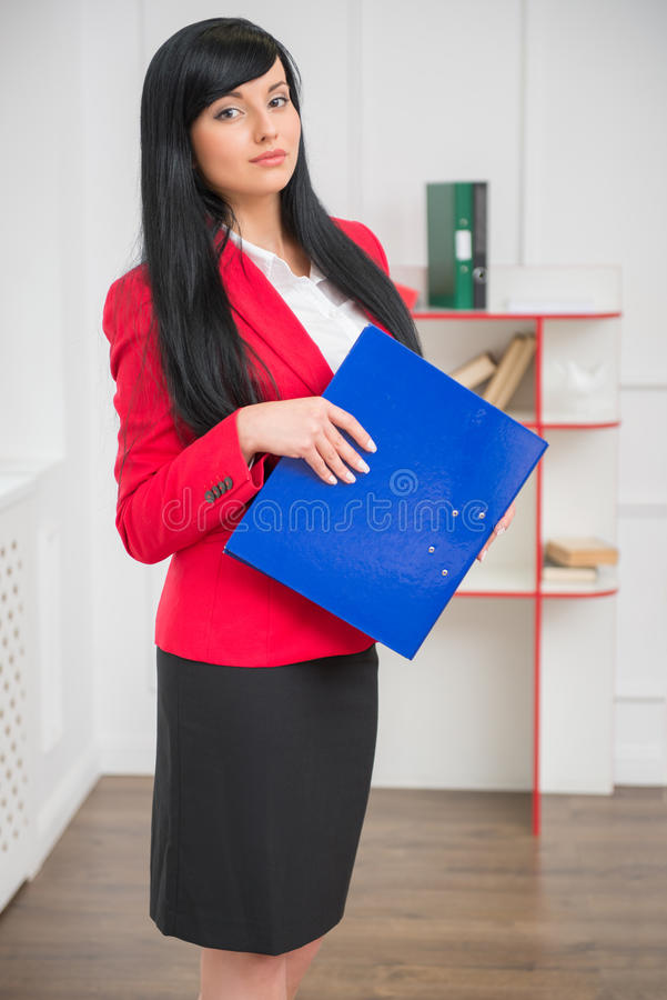 Young pretty business woman in red jacket. Vertical portrait of young confident business woman in red jacket standing in the office with a blue folder in her stock photos
