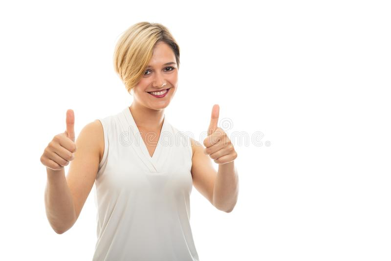 Young pretty business woman showing double thumb up. Gesture on black background with copypsace advertising area royalty free stock image