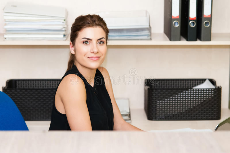 Young pretty business woman. Side view portrait of young businesswoman using computer at office desk stock photo