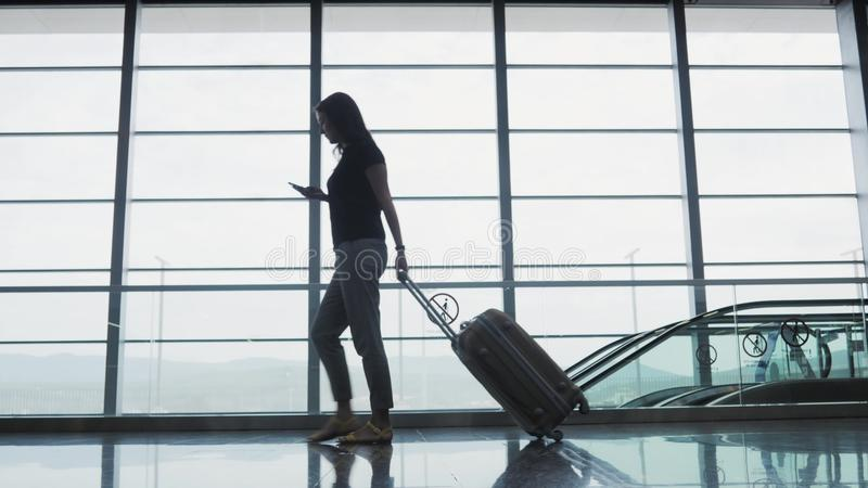 Young Pretty Businesswoman Using a Smartphone at Airport While Waiting Her Queue For Registration, Travelling Concept stock image
