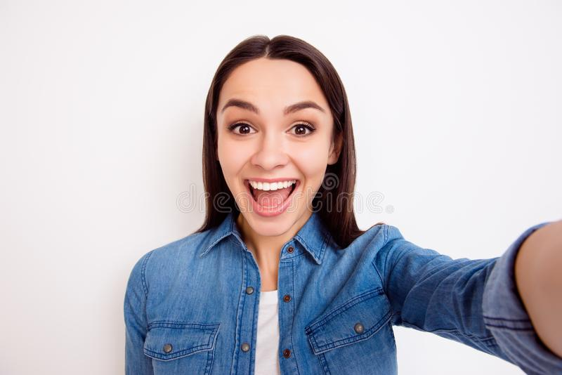 Young pretty cheerful girl in jeans shirt taking self-portrait royalty free stock photo